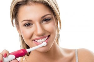 Smiling girl with electric toothbrush