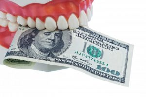 A denture holding a one-hundred dollar bill.
