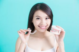 a woman holding Invisalign braces and a mold of traditional braces