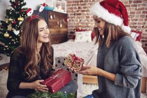 two women smiling exchanging gifts